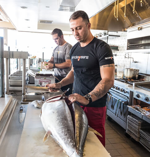 A chef at Tender Greens prepares a whole tuna fish in the kitchen.